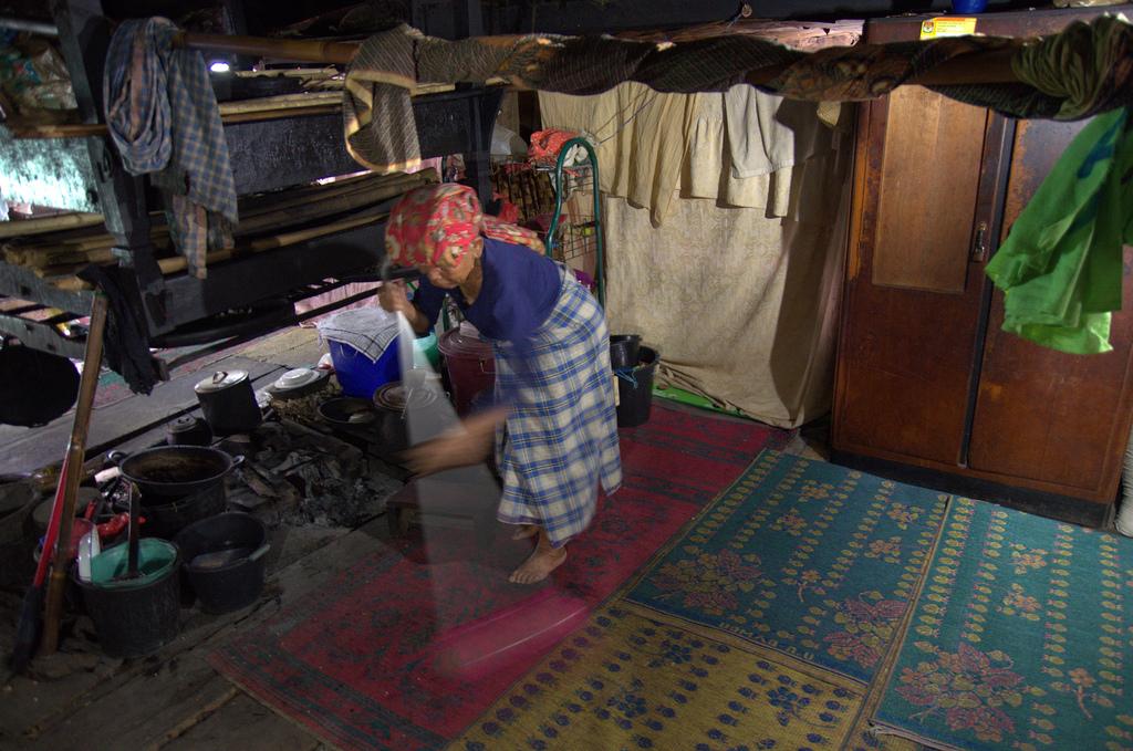Woman cleaning in Karo Batak house