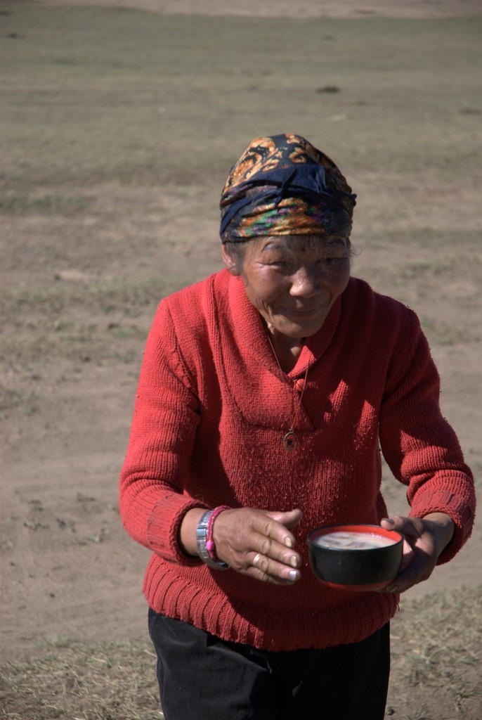 Mongolian woman carrying soup