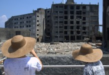 Japanese people looking at some buildings, Gunkanjima Hashima