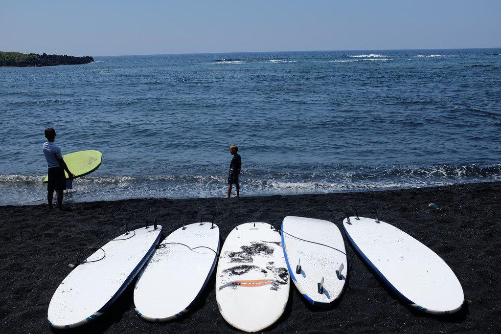 Surfborden op zwart lavastrand